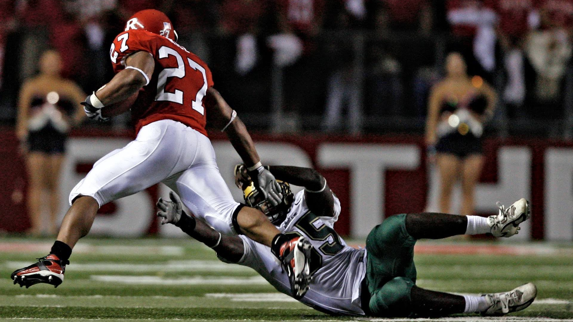A week after the Bulls beat West Virginia, Rutgers running back Ray Rice (27) stiffed-arms USF defensive end George Selvie and the team's hopes of contending for a national title. (Times, 2007)